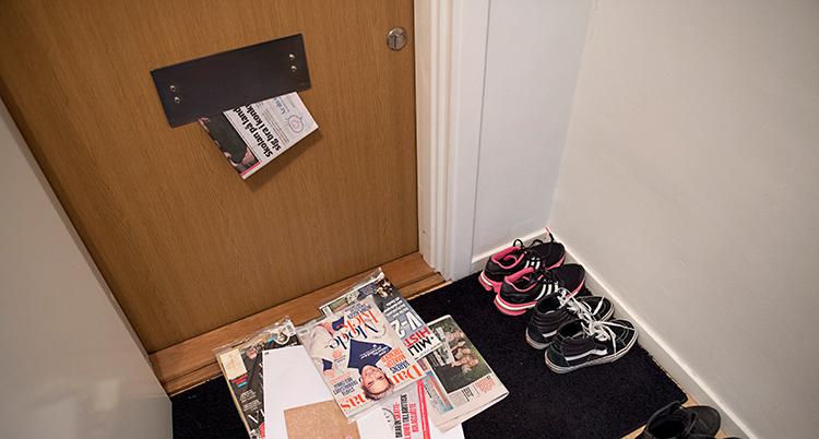 Vi är i hallen i en lägenhet. Bilden är tagen mot ytterdörren. Det ligger post på mattan. Och det kommer mer post genom brevinkastet.