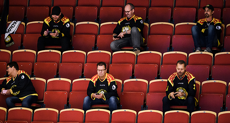 Några män sitter på läktaren. De kollar på en match i ishockey. De har stort avstånd mellan varandra.