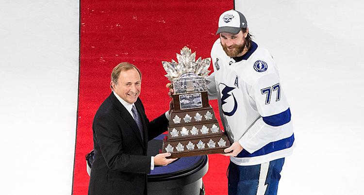 Två män står på en ishockeyplan. En äldre man står till vänster, i kostym. Han ger en stor pokal till mannen till höger. Mannen till höger har hockeydräkt och keps på sig.