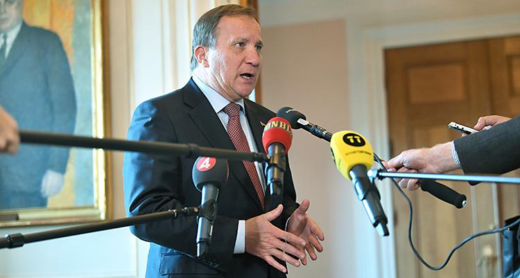 Stefan Löfven står och pratar. Han har kostym och slips. Journalister sträcker fram mikrofoner på långa pinnar.