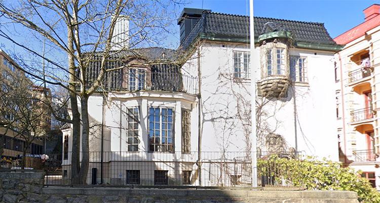 En bild på skolan. Huset är vitt med svart tak.