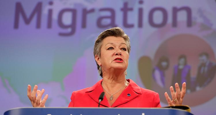 Ylva Johansson i röd kavaj på podiet. Hon är fotad underifrån och slår ut med händerna mitt i en mening. Bakom henne står ordet Migration på väggen.