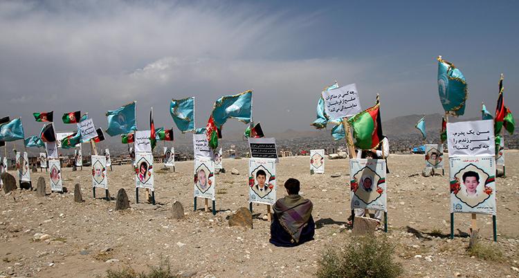 En pojke sitter på marken. På en rad framför honom är bilder på människor. Under bilderna är små gravstenar. Många flaggor vajar i bakgrunden.