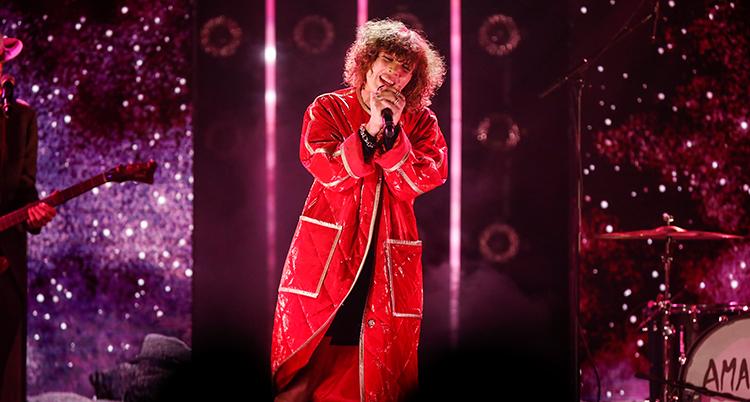 Hon står på en scen med en mikrofon i händerna. Hon har en röd lång kappa på sig.