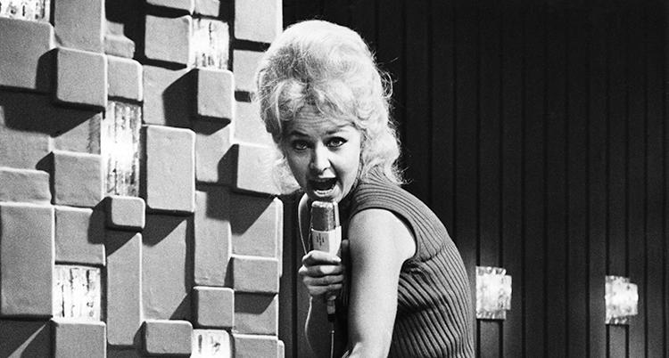 Hon har en mikrofon i handen och ljust tuperat hår. Hon sjunger och munnen är öppen.