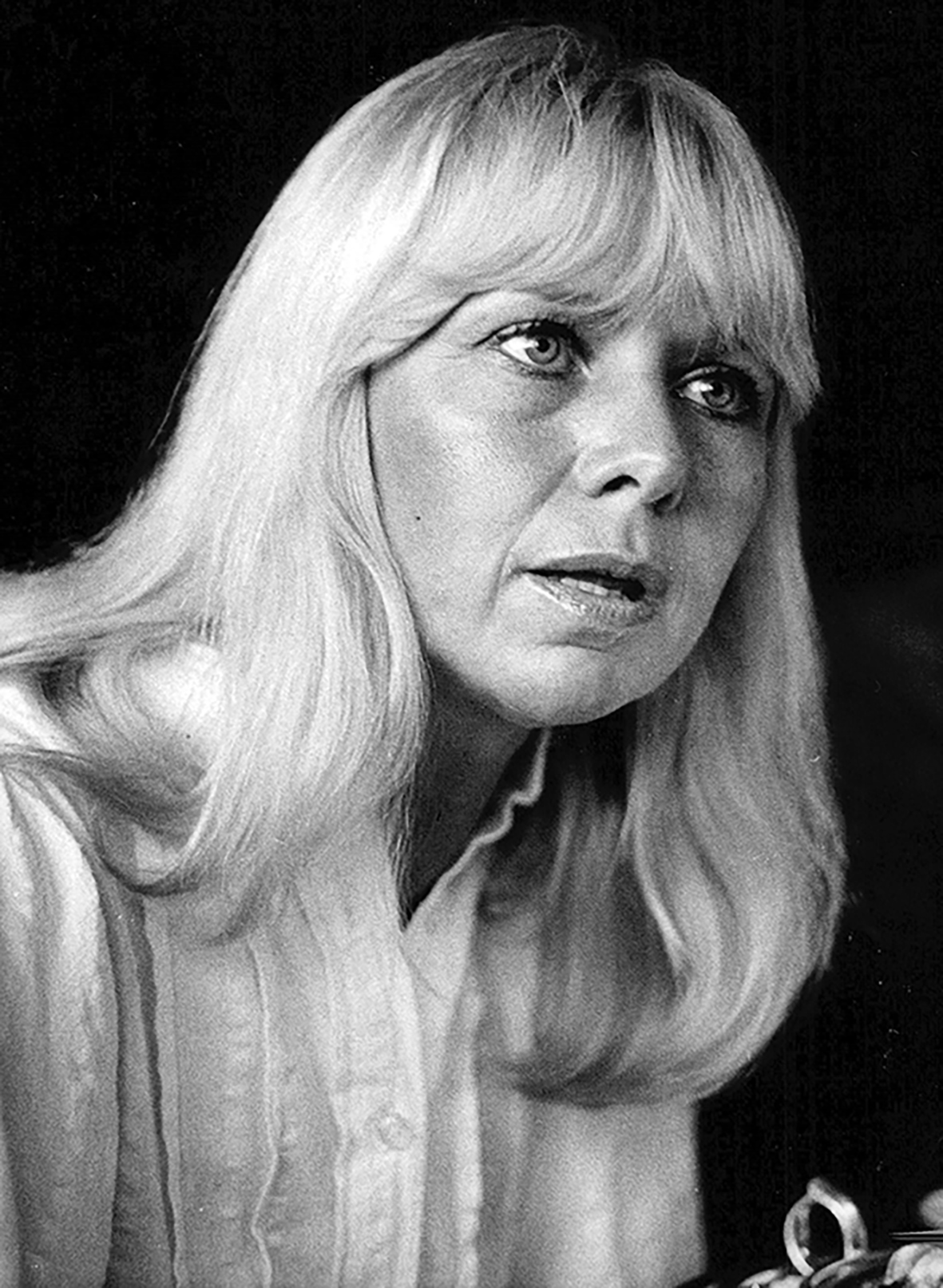 En nära bild på Anita Lindblom. Hon har ljust utsläppt hår. Hon ser allvarlig ut.