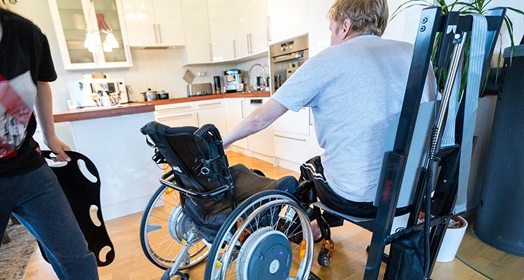 en person står bredvid en person som ska sätta sig i en rullstol. allt händer i ett kök.