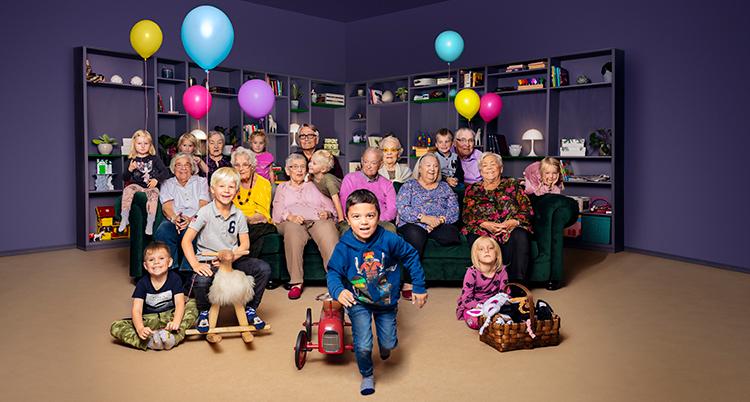 Många gamla och barn sitter tillsammans.