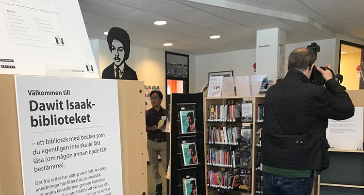 Hyllor med böcker. En skylt med Dawit Isaaks ansikte syns också på en vägg.