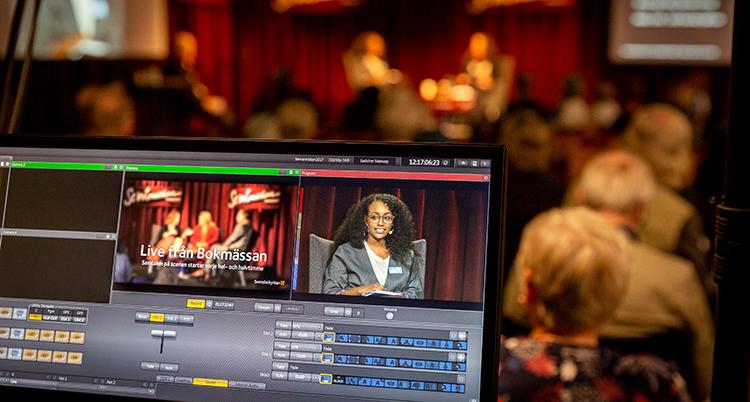 En datorskärm med ett program för inspelning. I bakgrunden syns en scen där två sitter och pratar med varandra.