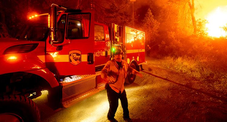 En brandman och en bil. I bakgrunden brinner en skog.