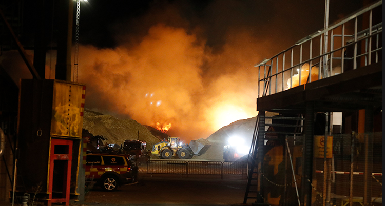 Bilden är tagen en bit ifrån branden. Men lågor syns bakom de stora högarna. Himlen lyser av lågorna.