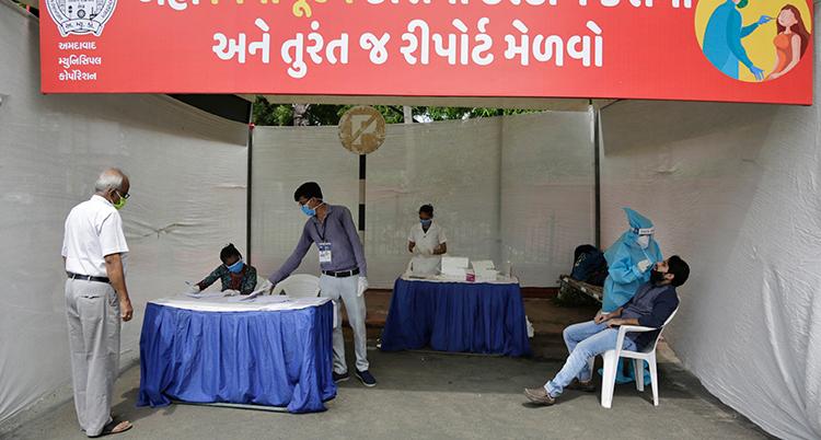 En plats för provtagning för corona viruset i Indien. Flera personer med munskydd.