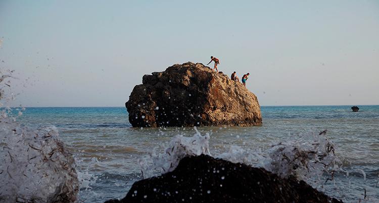 Några badar i havet. De står på en stor sten.