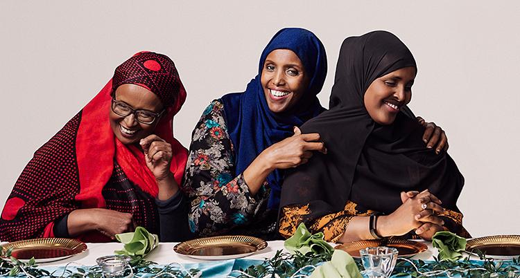 De tre kvinnorna sitter vid ett dukat bord. De ler. De har alla slöjor på huvudet i olika färger.