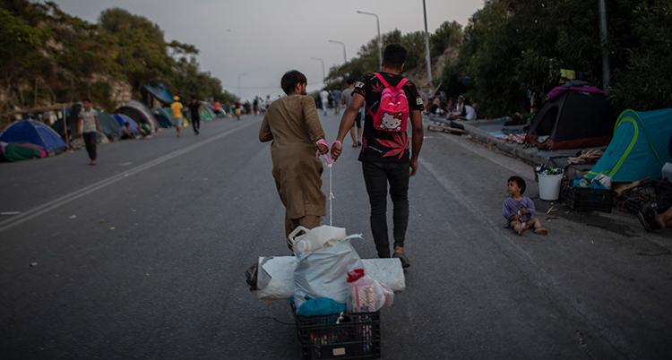 Två personer drar en liten korg med packning på en gata i Lesbos.
