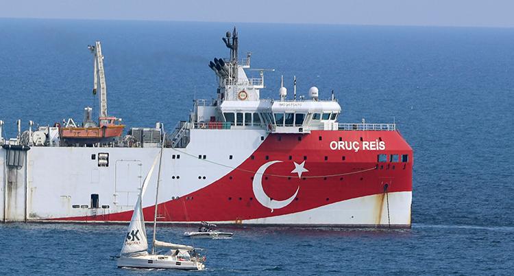 Ett stort fartyg. Det är rött och vitt med Turkiets symbol, en halvmåne och en stjärna, målat på det röda. Framför skeppet är en liten segelbåt.