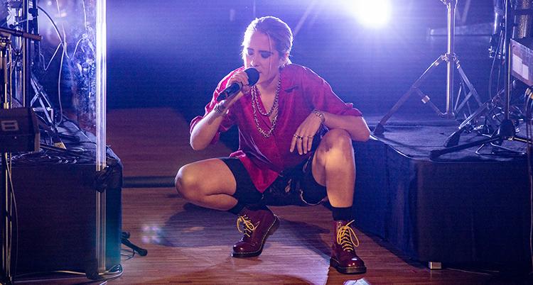 Hon står på huk på en scen med en mikrofon i handen. Hon har en röd skjorta och svarta cykelbyxor på sig.