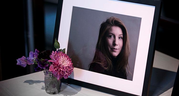 Ett inramat foto på Kim Wall på en bänk. Framför står en liten glasvas med en blomma.