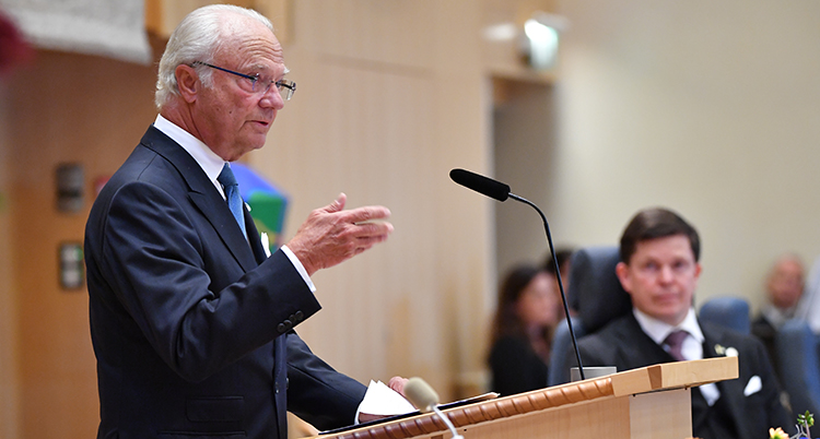 Kungen står i talarsolen. Han pekar med en hand. Bilden är tagen från sidan. I bakgrunden syns talmannen lite suddigt.