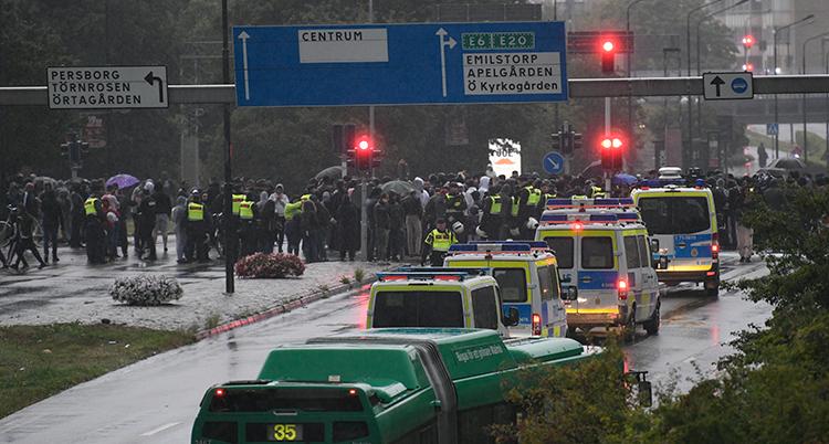 Flera polisbilar och poliser står på en regnig gata. Bakom dem syns en massa människor på långt håll.