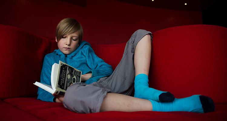 Ett barn ligger ner på en röd soffa. Barnet läser en bok.