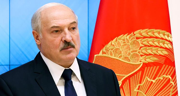 Aleksandr Lukasjenko framför landets flagga.