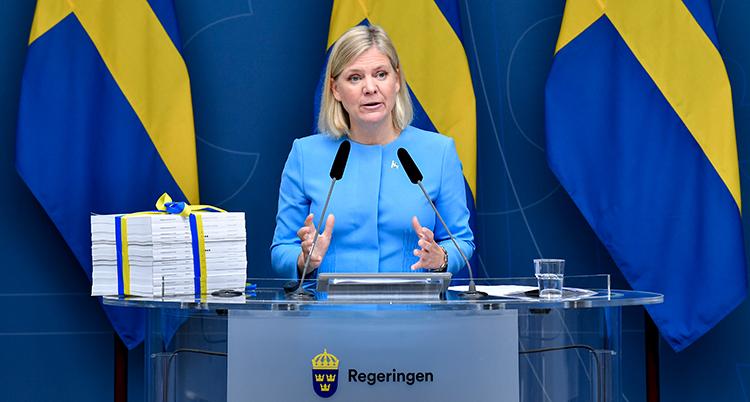 Andersson står i en talarstol. Bakom henne är svenska flaggor. Bredvid henne ligger alla förslag i en tjock biunt. Ett blågult snöre är knuten runt bunten.