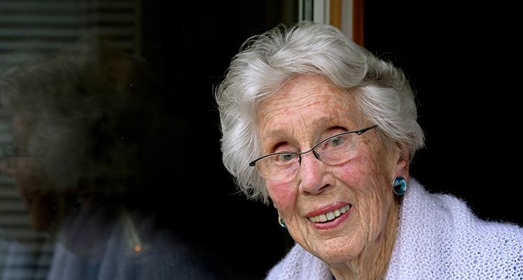 En nära bild på Maria. Hon ler och tittar in i kameran. Hoon har kort, lockigt och grått hår.