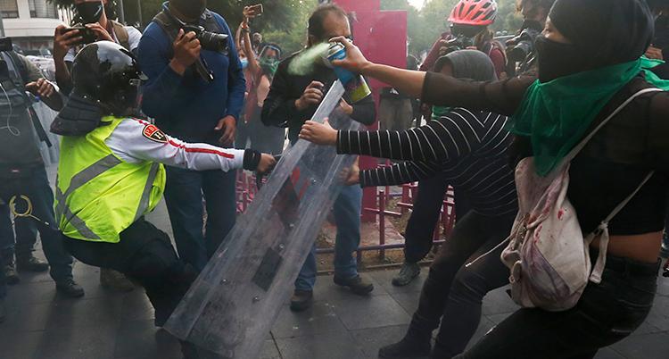En polis tår med en sköld. Ett par kvinnor med masker för ansiktet försöker att dra den ifrån honom.