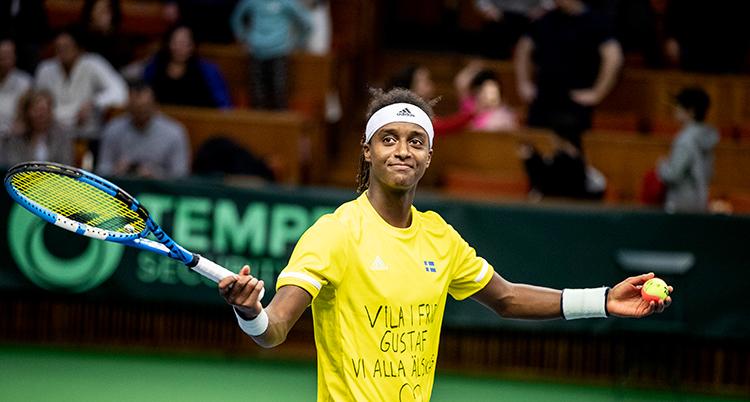 Mikael Ymer har gul tröja och ett vitt hårband. Han ler och håller ett racket i ena handen.