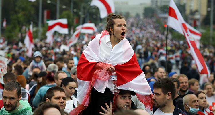 Massor av människor syns på bilden. En kvinna har en röd och vit flagga runt kroppen.