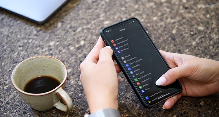 En kaffekopp och en mobil syns i bild. I mobilen syns en lista med olika appar.