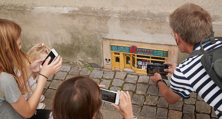 Tre personer tar bild på den lilla affären med sina mobiltelefoner.