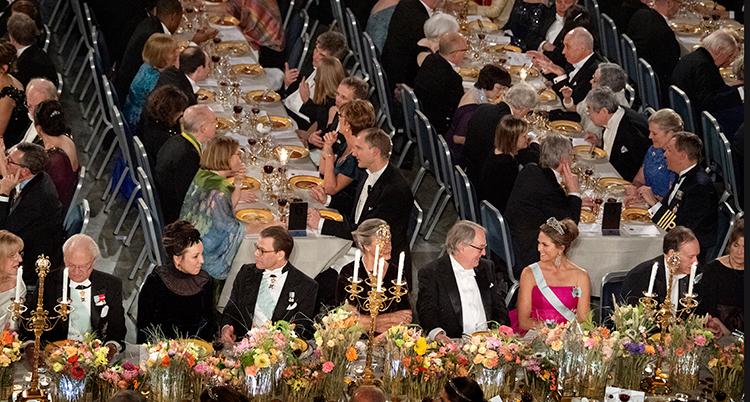 Bilden är tagen ovanifrån. Många människor sitter vida långa bord och äter. Massor av blommor syns på borden.
