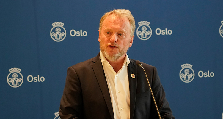 Han har vit skjora och kavaj. Han talar i en mikrofon. Bakom honom står det Oslo på en vägg.