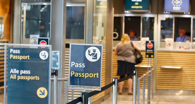 En kvinna står vid en lucka med ryggen mot kameran. Hon har gått förbi skyltar där det står Pass och Passport. Hon är vid gränsen på Arlanda.