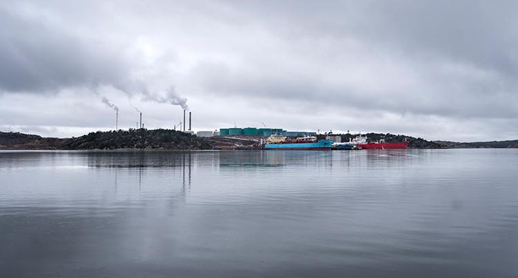 Flera stora båtar syns på havet. Fabriken syns i bakgrunden. Det ryker från fabrikens skorstenar.
