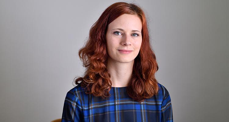 Rebecka le Moine har rött axellångt hår och blårutig skjorta. Hon tittar in i kameran och ler.