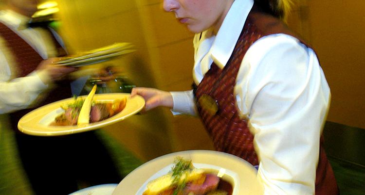 en kvinna bär två tallrikar på en restaurang.