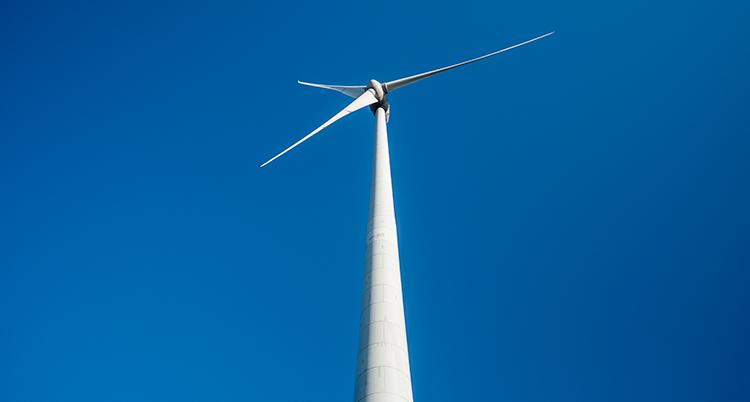 En pelare till ett vindkraftverk fotat underifrån. Högst upp är själva snurran. Bakgrunden är en djupblå himmel.
