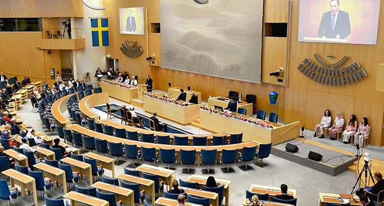 En bild somvisar en stor del av riksdagen. Politikerna sitter i sina bänkar. Statsministern står i talarstolen. En bild av honom visas på en skärm.