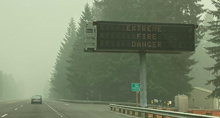 Extremt stor fara för brand står det på skylten. En väg kör på vägen. Luften är täckt av rök.