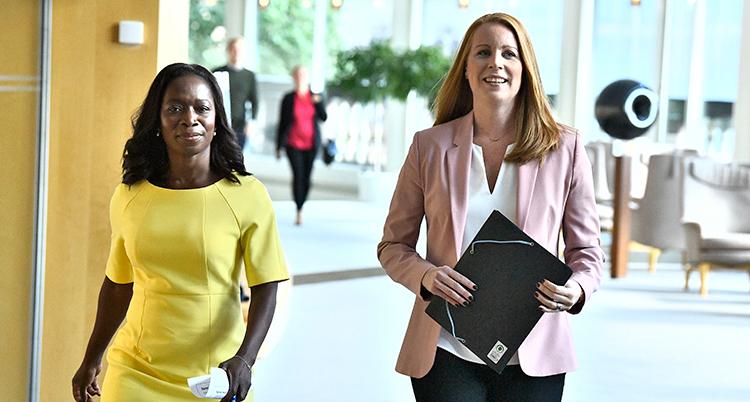De två kvinnorna går bredvid varandra. Den ena har en gul klänning på sig. Den andra har en rosa kavaj.