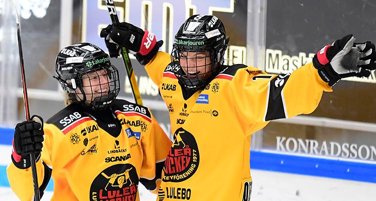 Två spelar i gula dräkter ser glada ut. de sträcken armarna i luften.