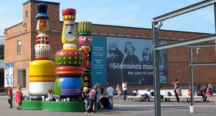 Färgglada stora figurer står utanför en stor byggnad.