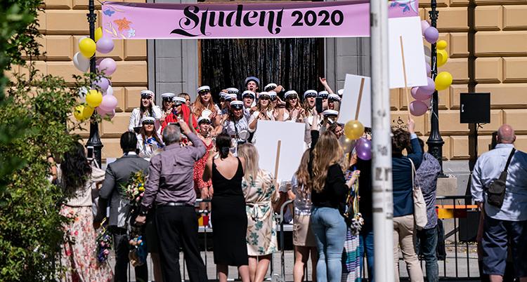Ett gäng med studenter firar på en trappa med sina mössor på. Folk står runt dem med ballonger och skyltar.