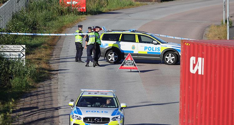 Två polisbilar och flera poliser syns på platsen. De sätter upp tejp för att stänga området.