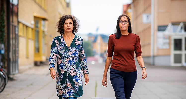 De två kvinnorna går bredvid varandra på gatan.
