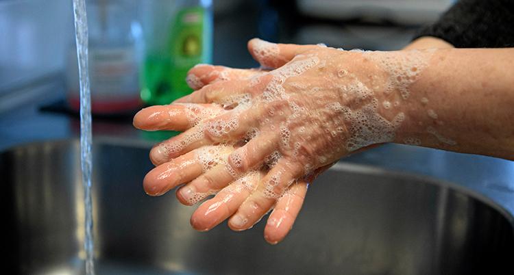 Ett par händer har skum av tvål på sig. En kran med vatten syns i bakgrunden.